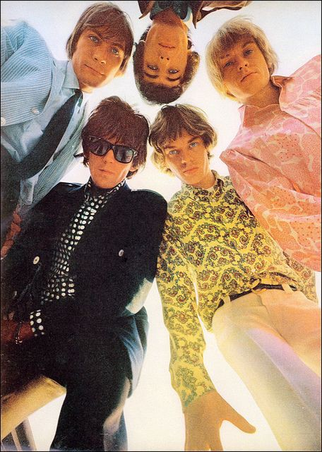 The Rolling Stones (1966) huddled together in a circle—looking downwards at the camera.