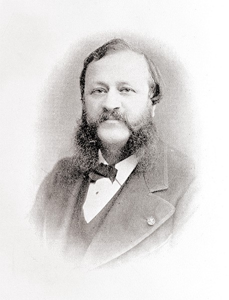 Evans as a younger man. He has a plump face, ear-length hair, and famously huge mutton-chop whiskers.