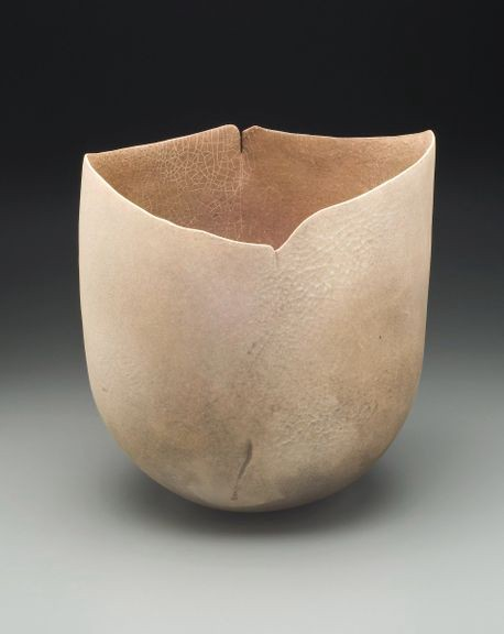 Glazed earthenware vessel in sandy tones with a raw, organic texture.