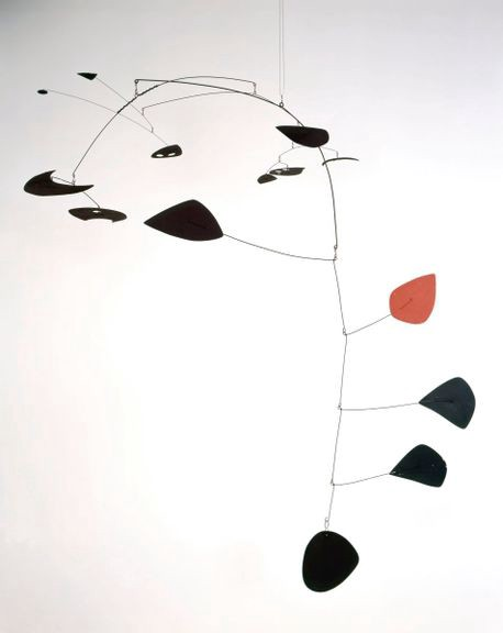Mobile with black and red shapes by Alexander Calder hanging in a somewhat vertical orientation.