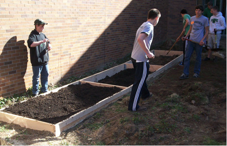 Image of students cleaning building raised beds
