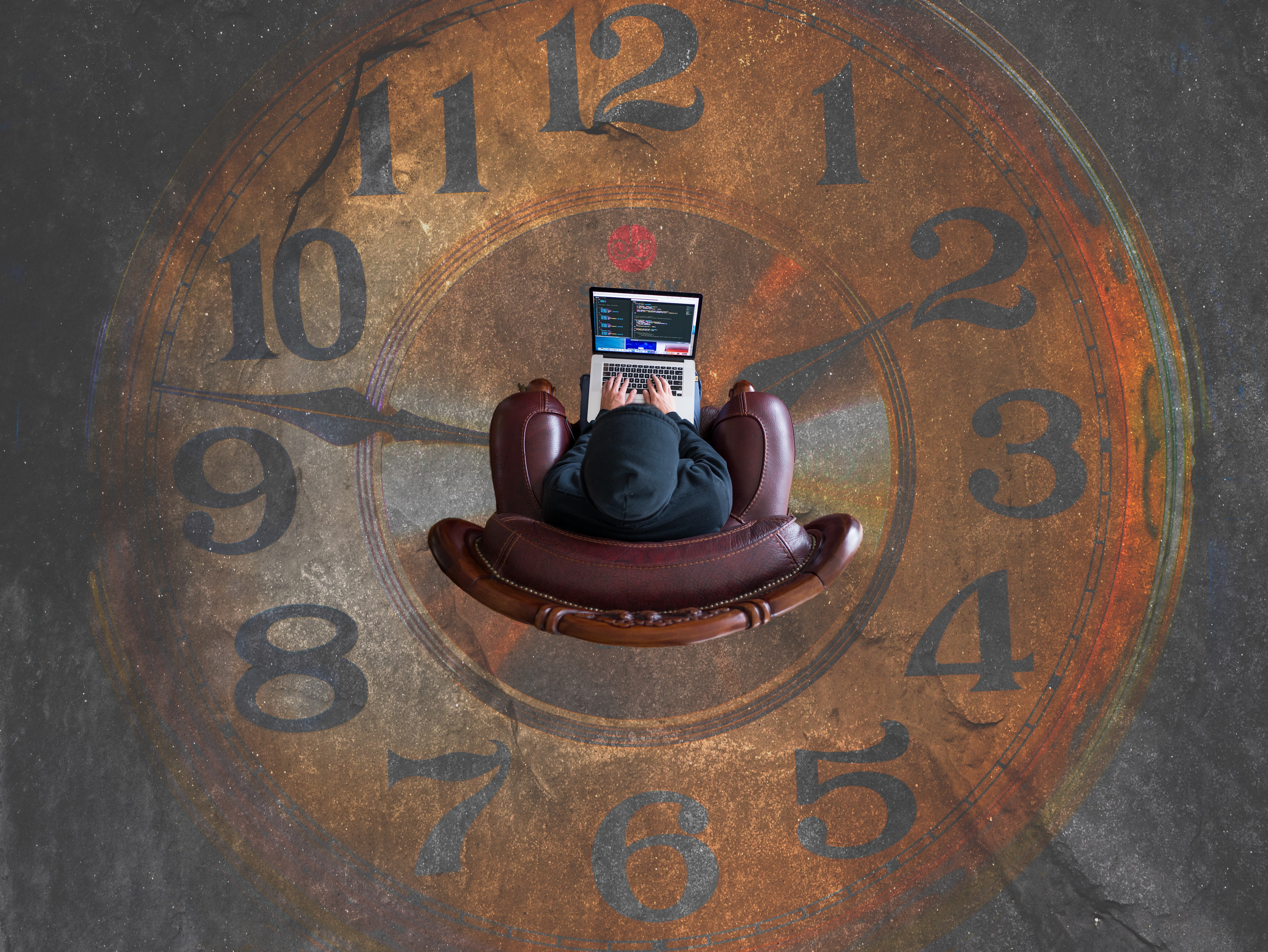 Person sitting on chair wearing hoodie, working on laptop. View is from above. Person is inside a clock. The time points 1:50
