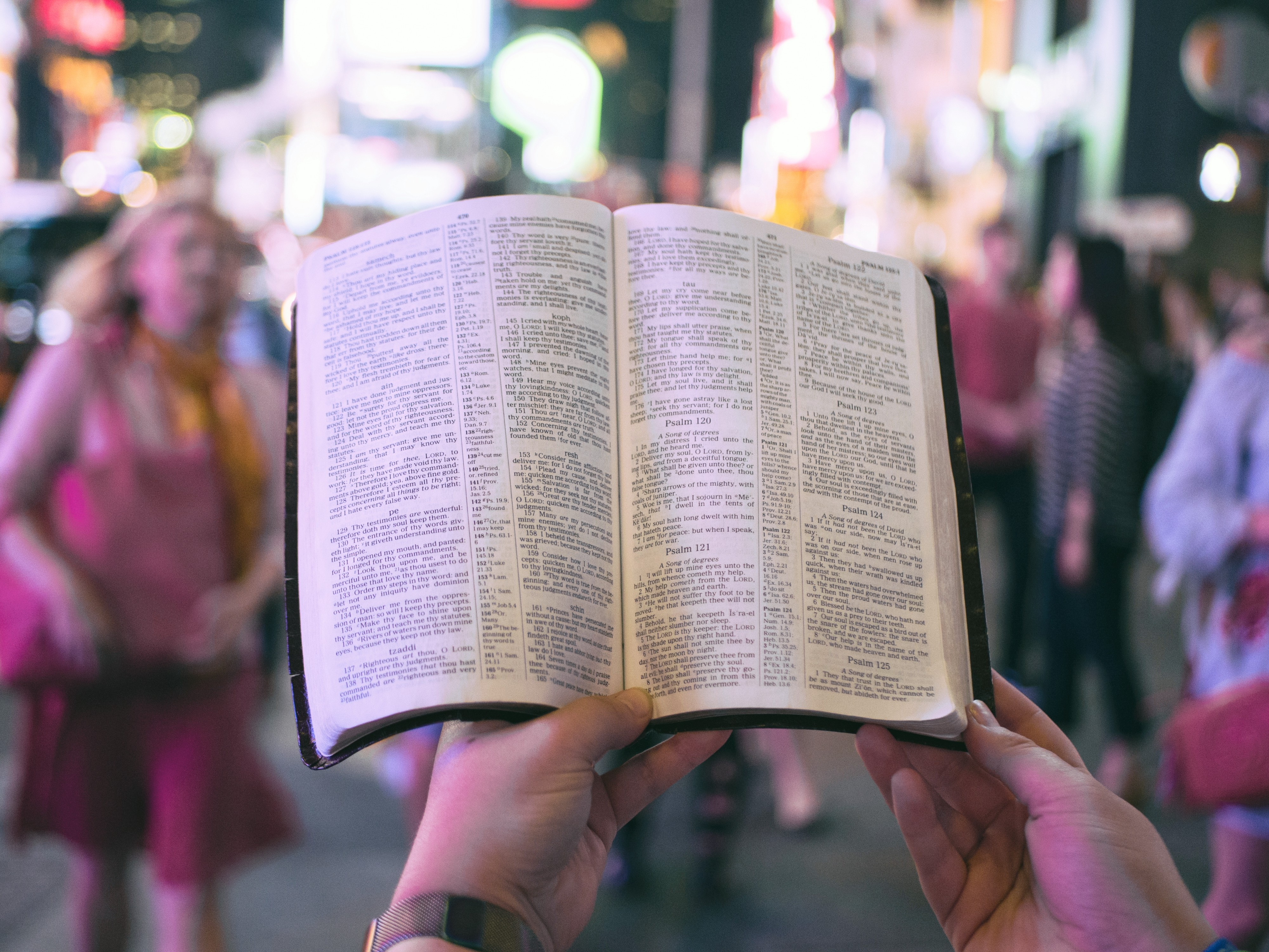 A person's hands holding a Bible, with a crowded street scene in the background
