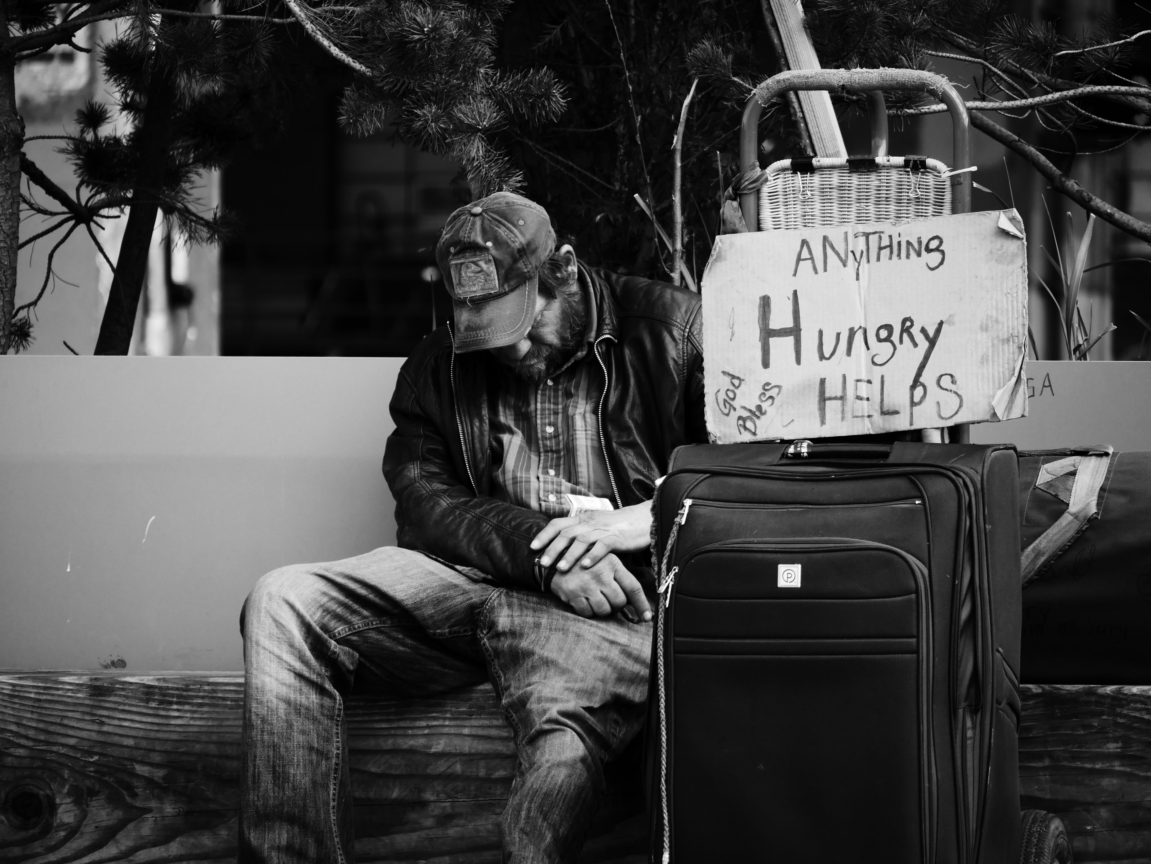Homeless, poor, hungry man with sign asking for help with food or money.