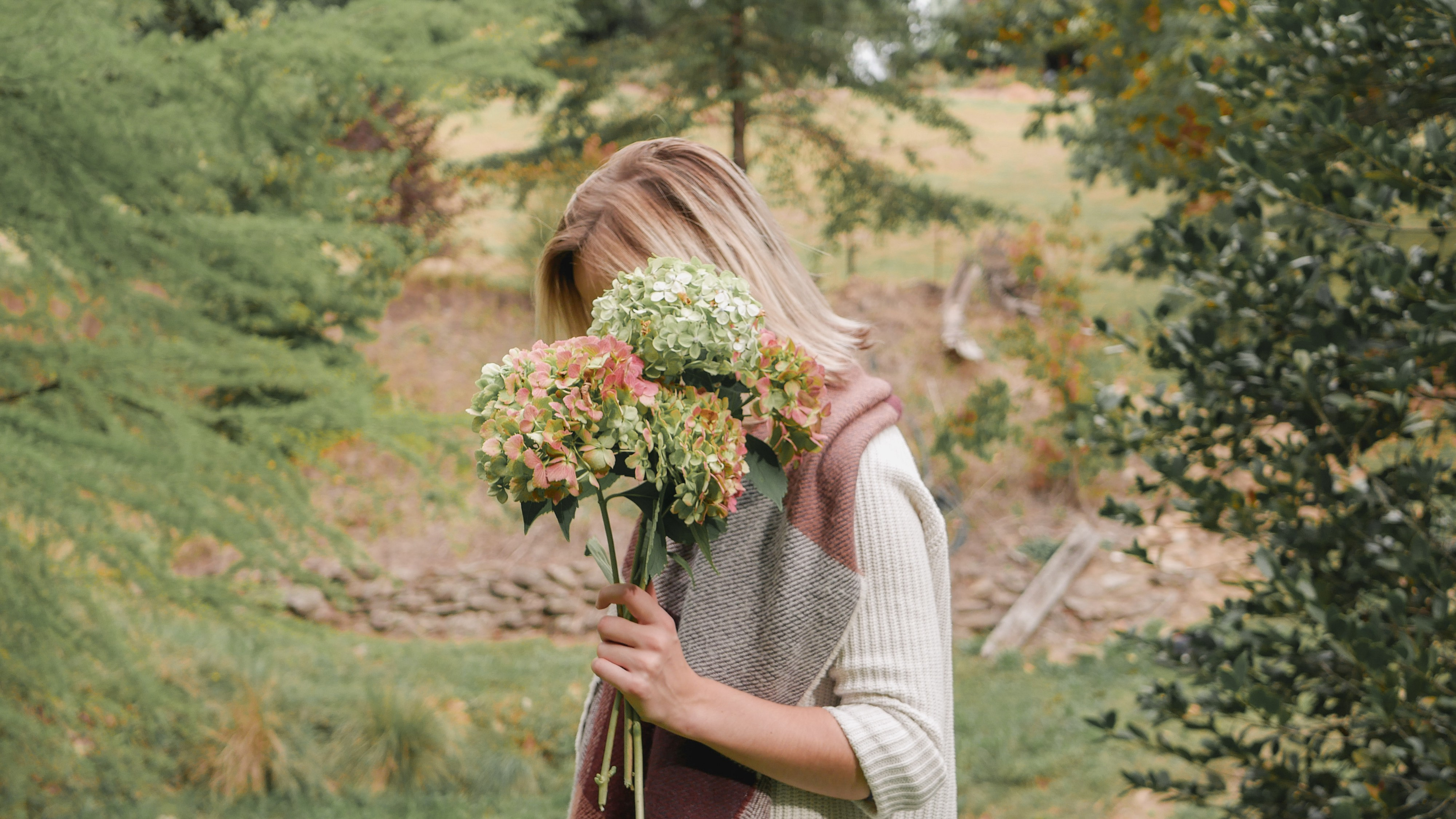 A woman holding a bunch of hydrangeas on a cool day