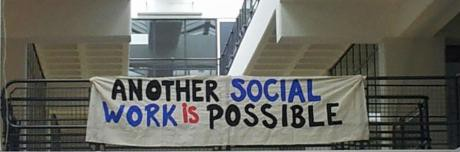 """A banner hanging over a railing that reads """"Another Social Work is Possible"""" in blue, black, and red lettering."""