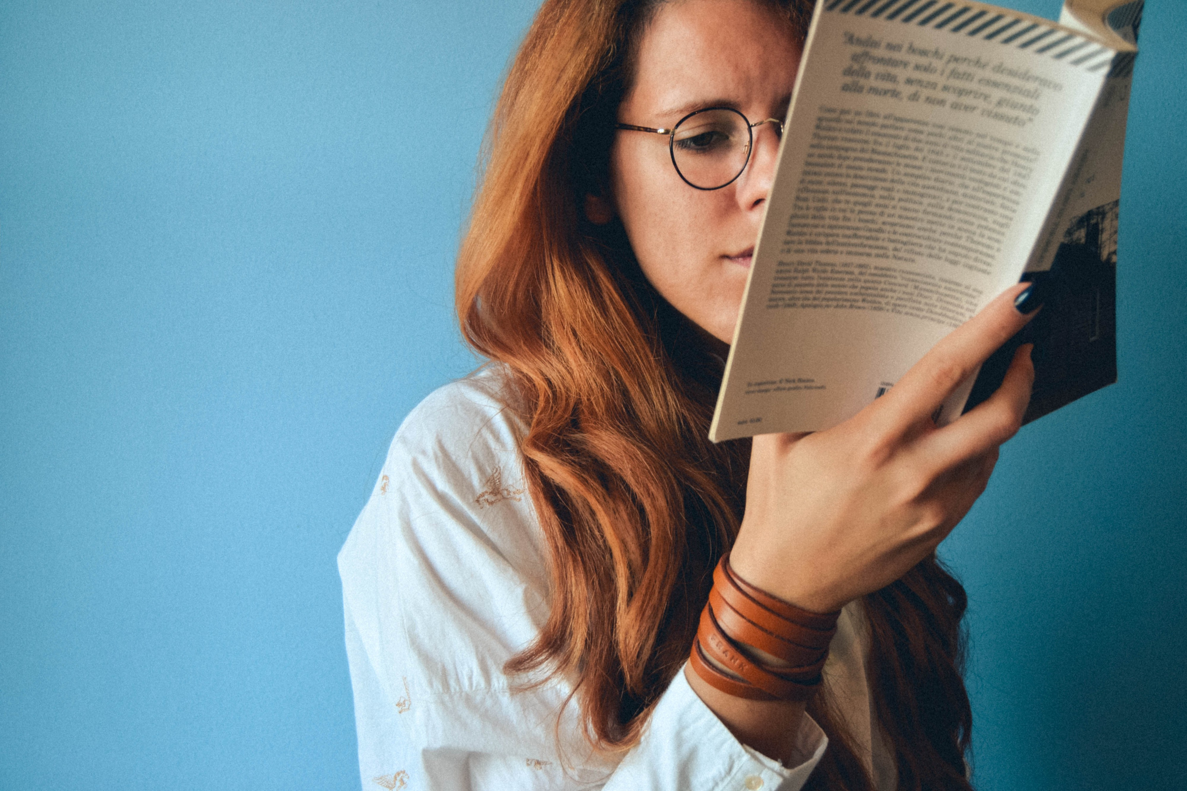 Red haired woman wearing glasses, reading a book.