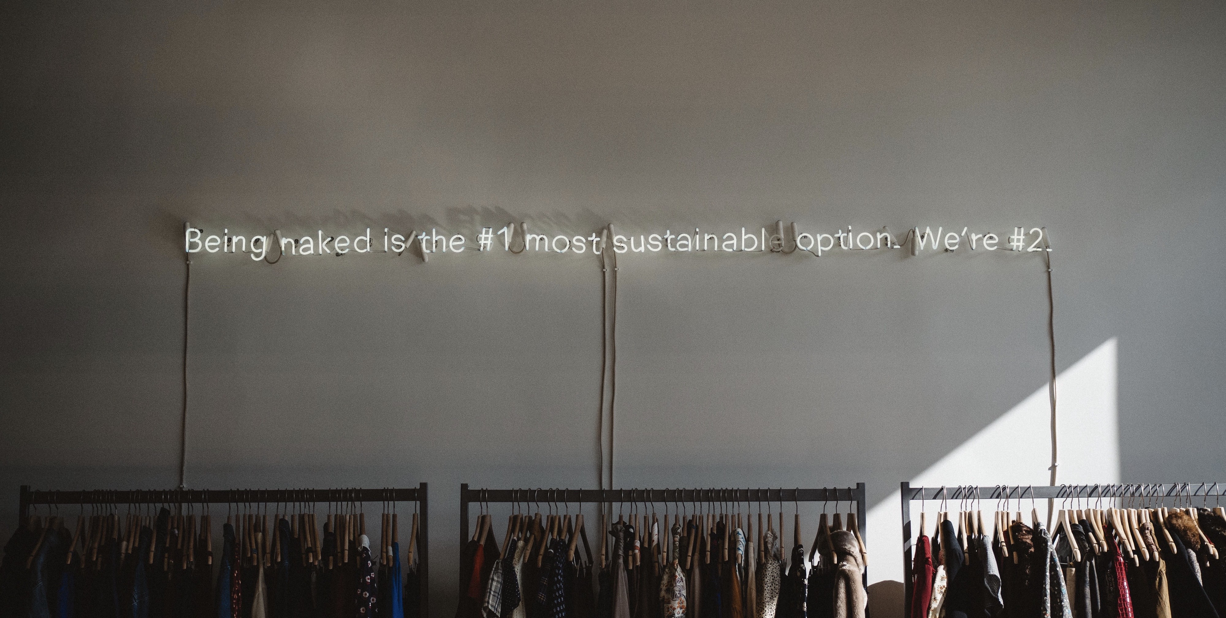 """Photo of a wall with a lit up sign that reads: """"Being naked is the #1 most sustainable option. We're #2"""" above clothing racks"""