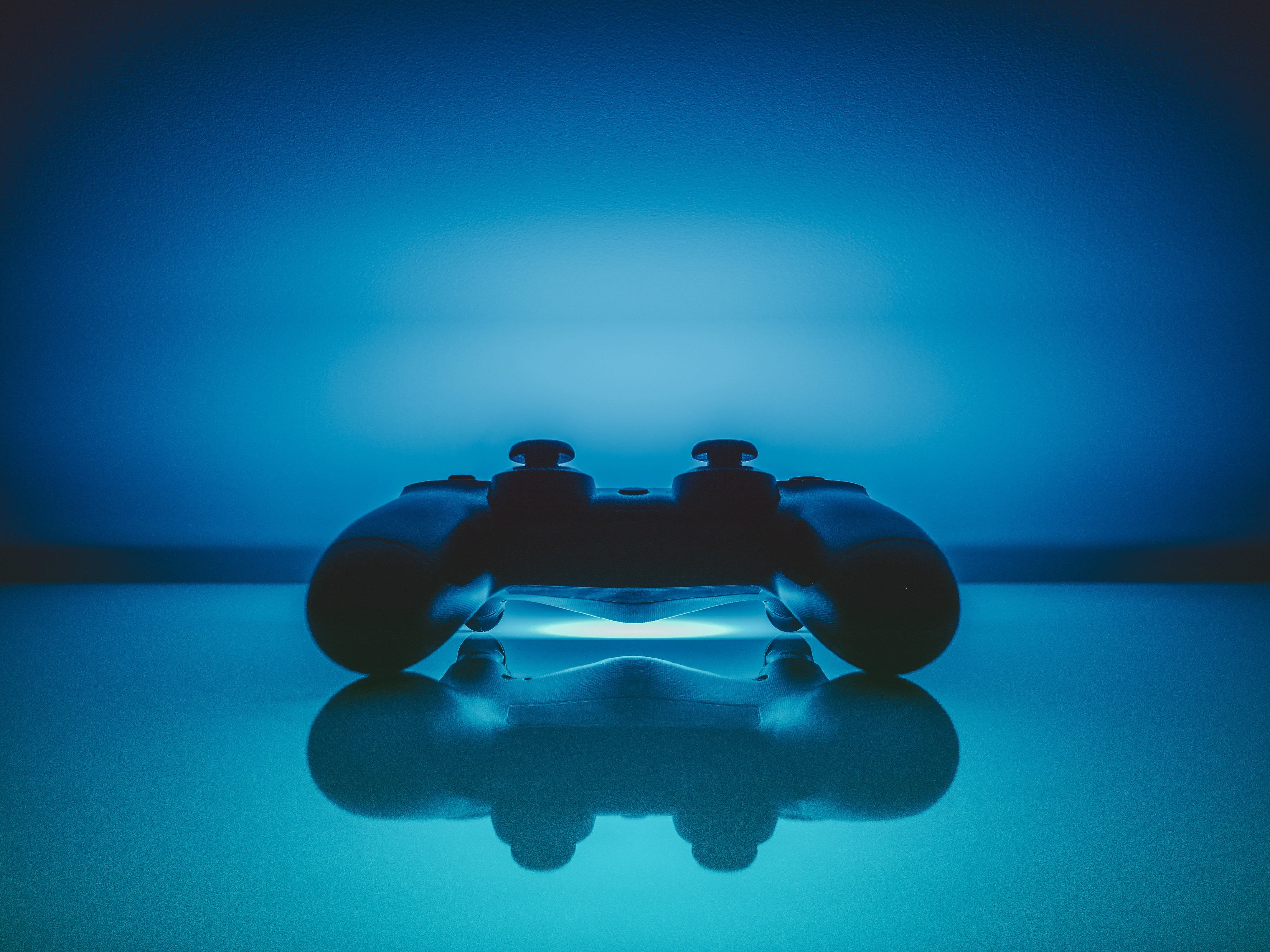 A video gaming controller with an interesting blue background.
