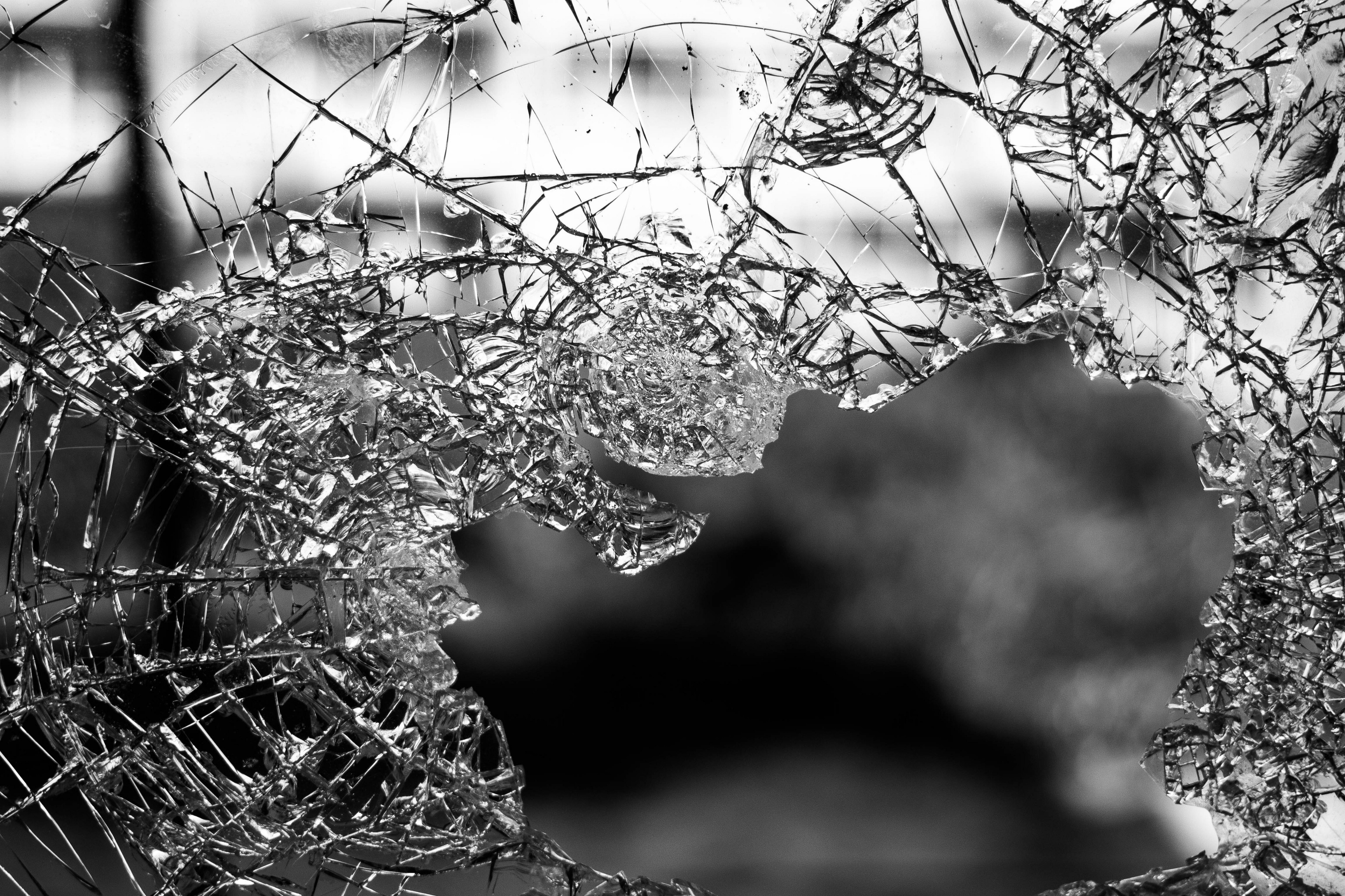 A shot of broken glass with a blurred background looking through a hole smashed into the glass.