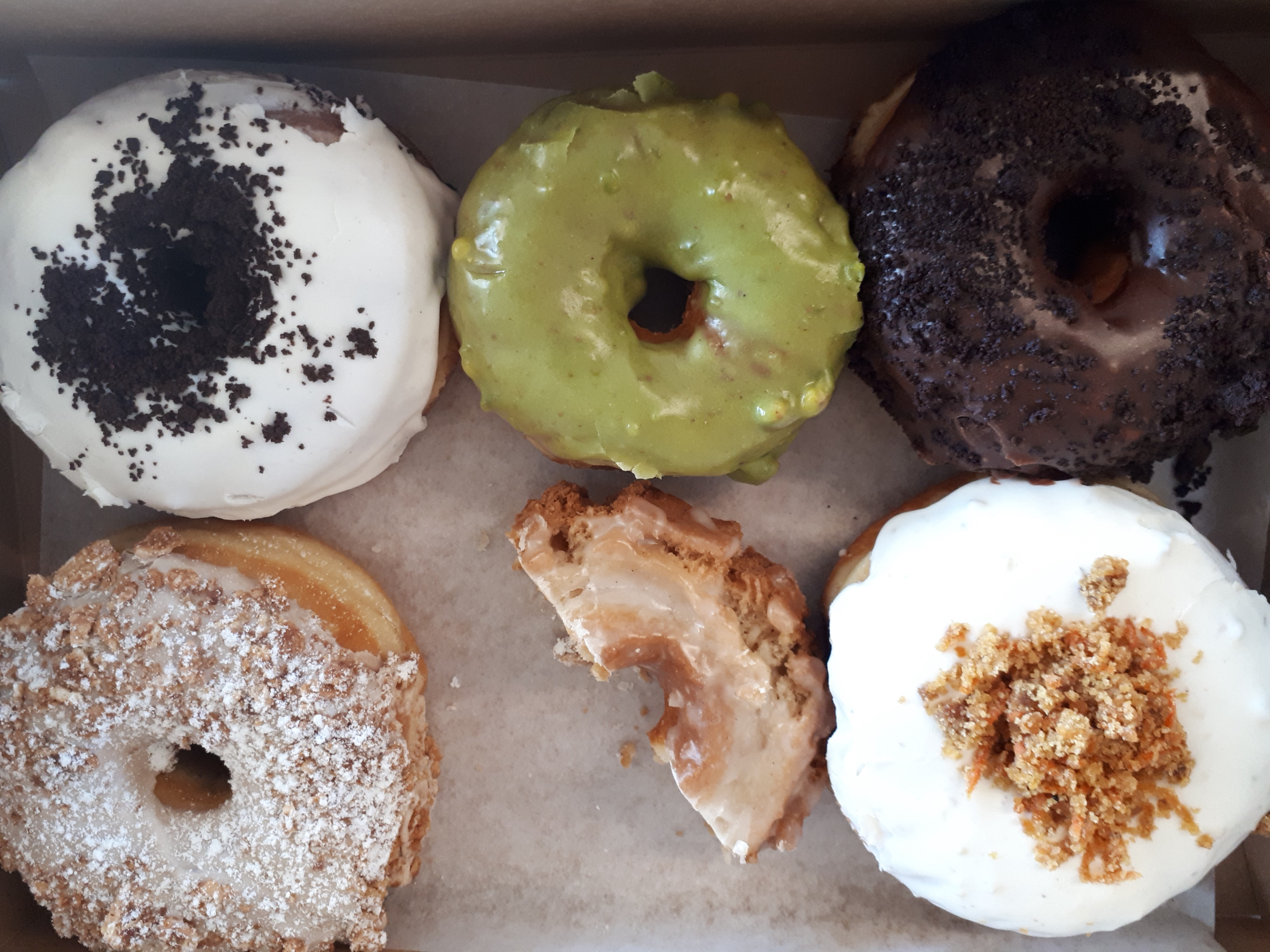 A photo of 6 colourful doughnuts; one is half eaten.