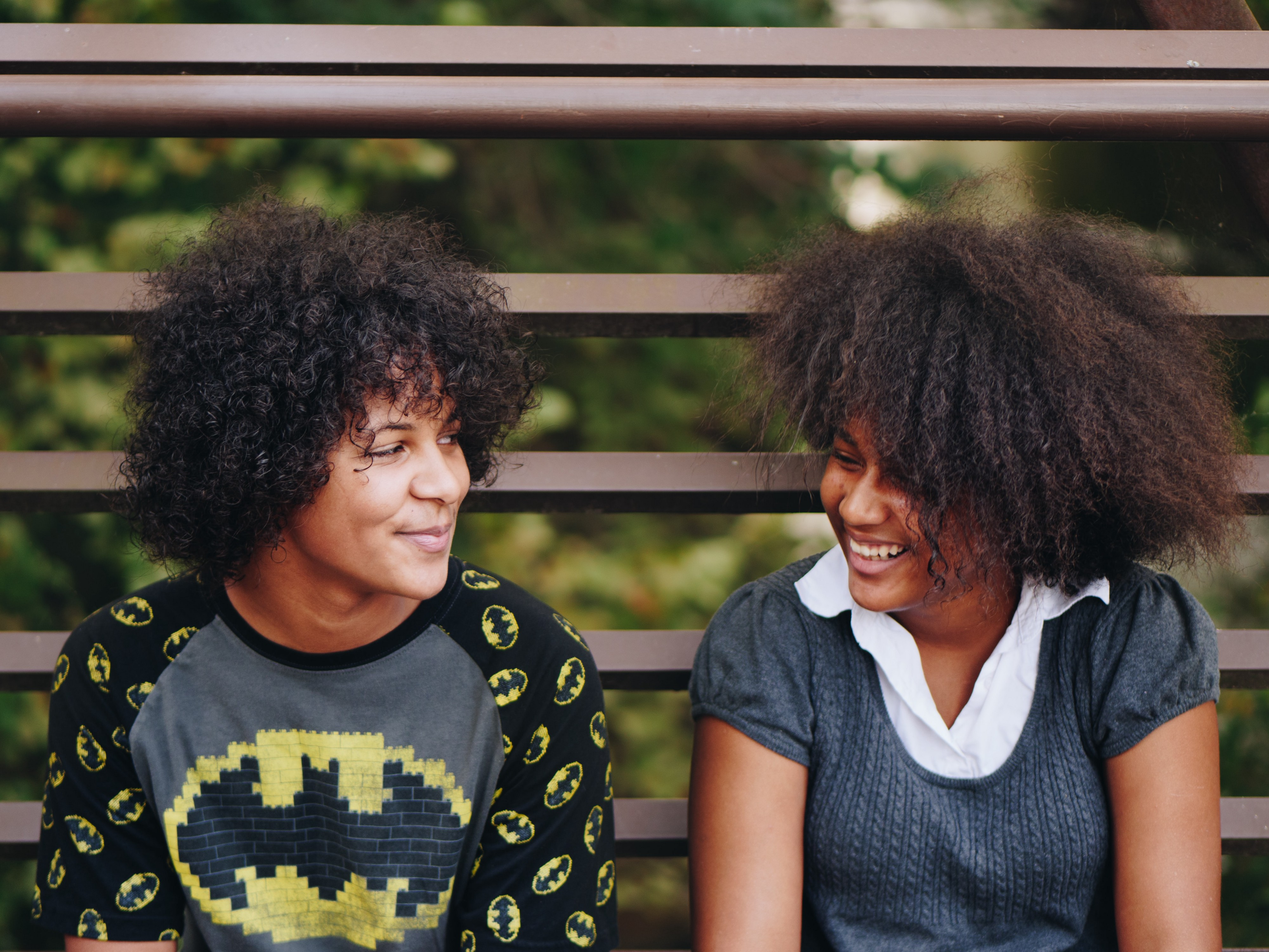 Two teenagers sitting on bleachers, smiling at each other.