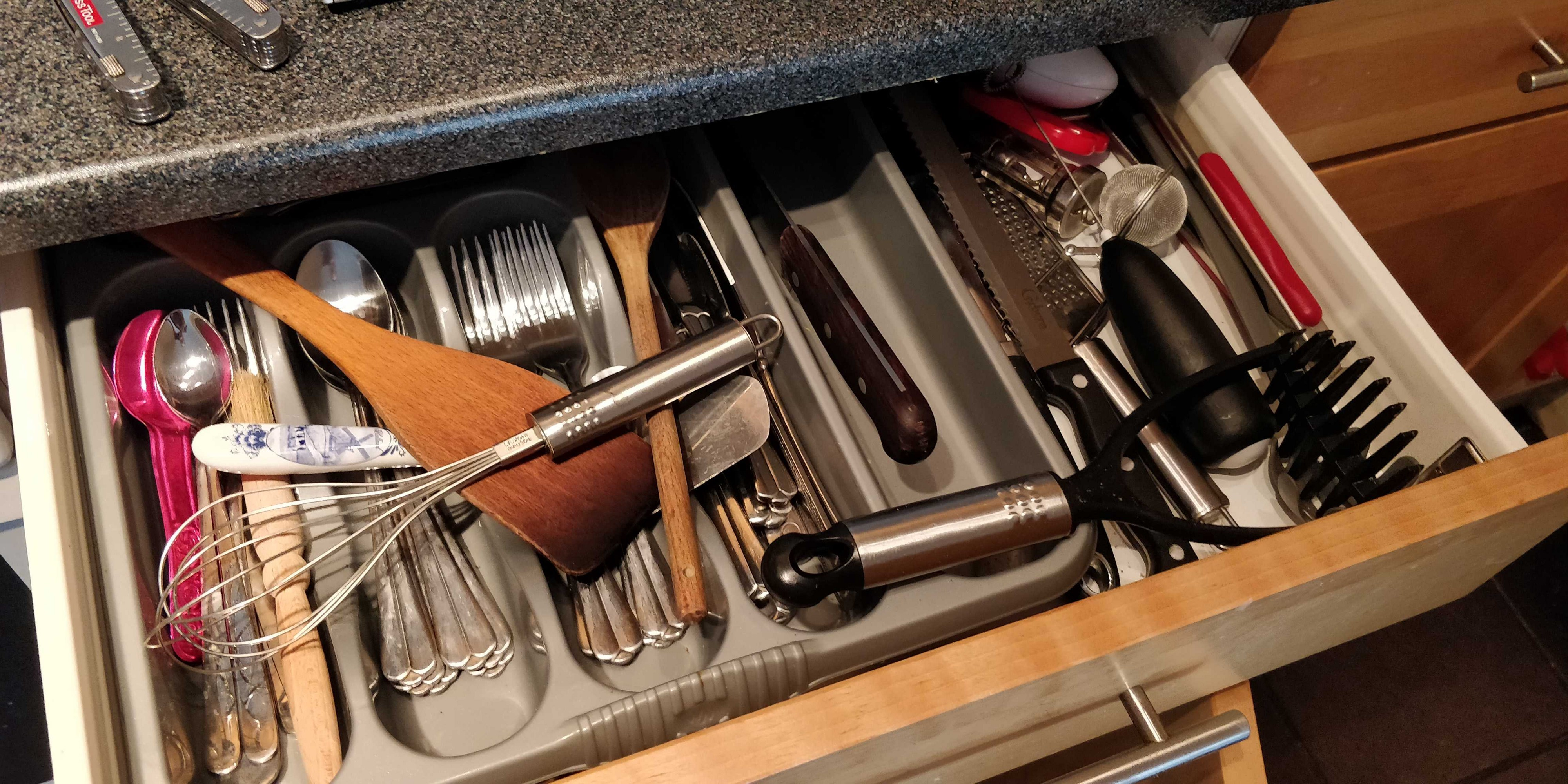 View of an open cutlery drawer, with the offending knife still lodged in the back of the drawer.