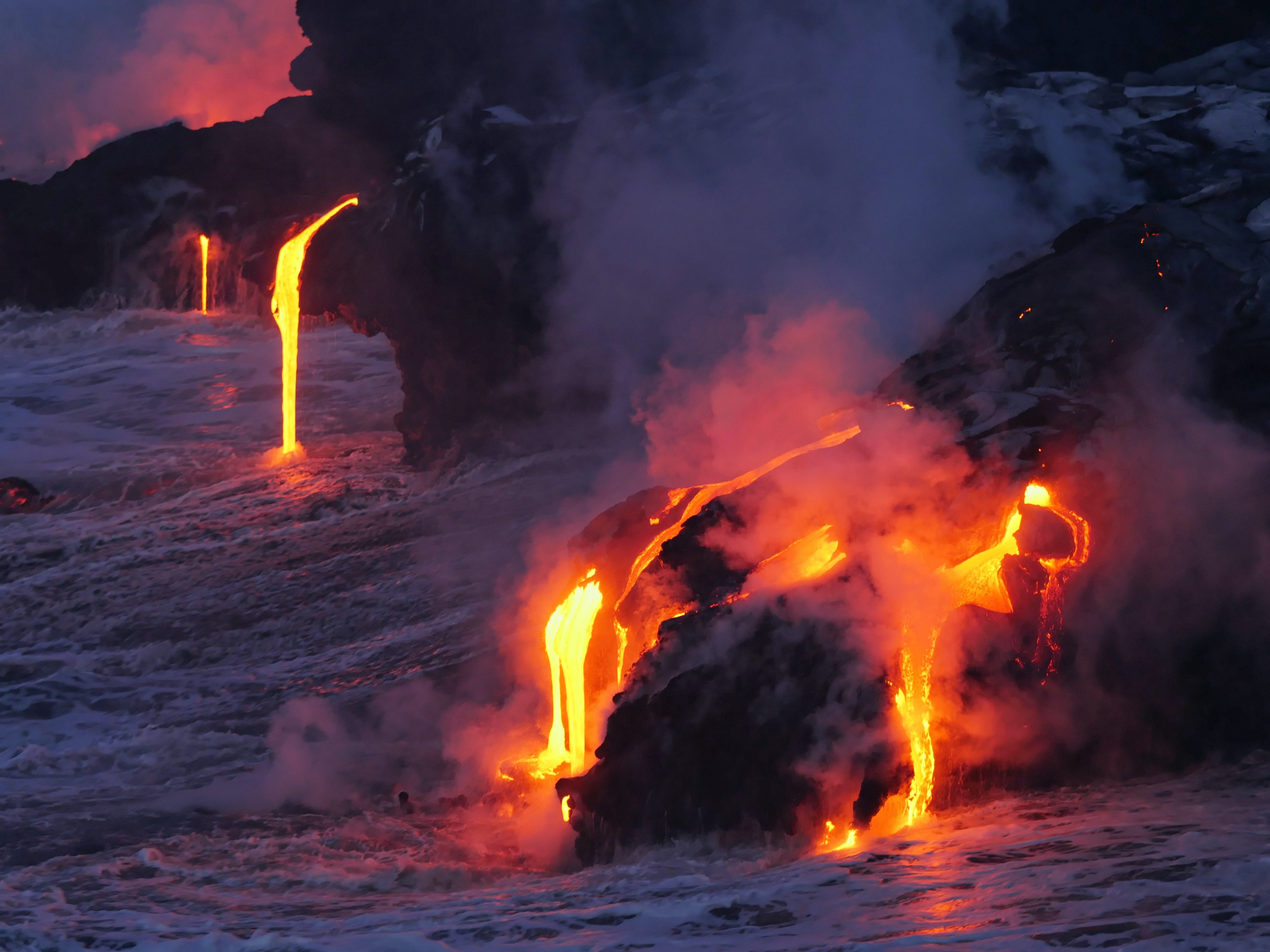Lava from an erupting volcano entering the ocean.