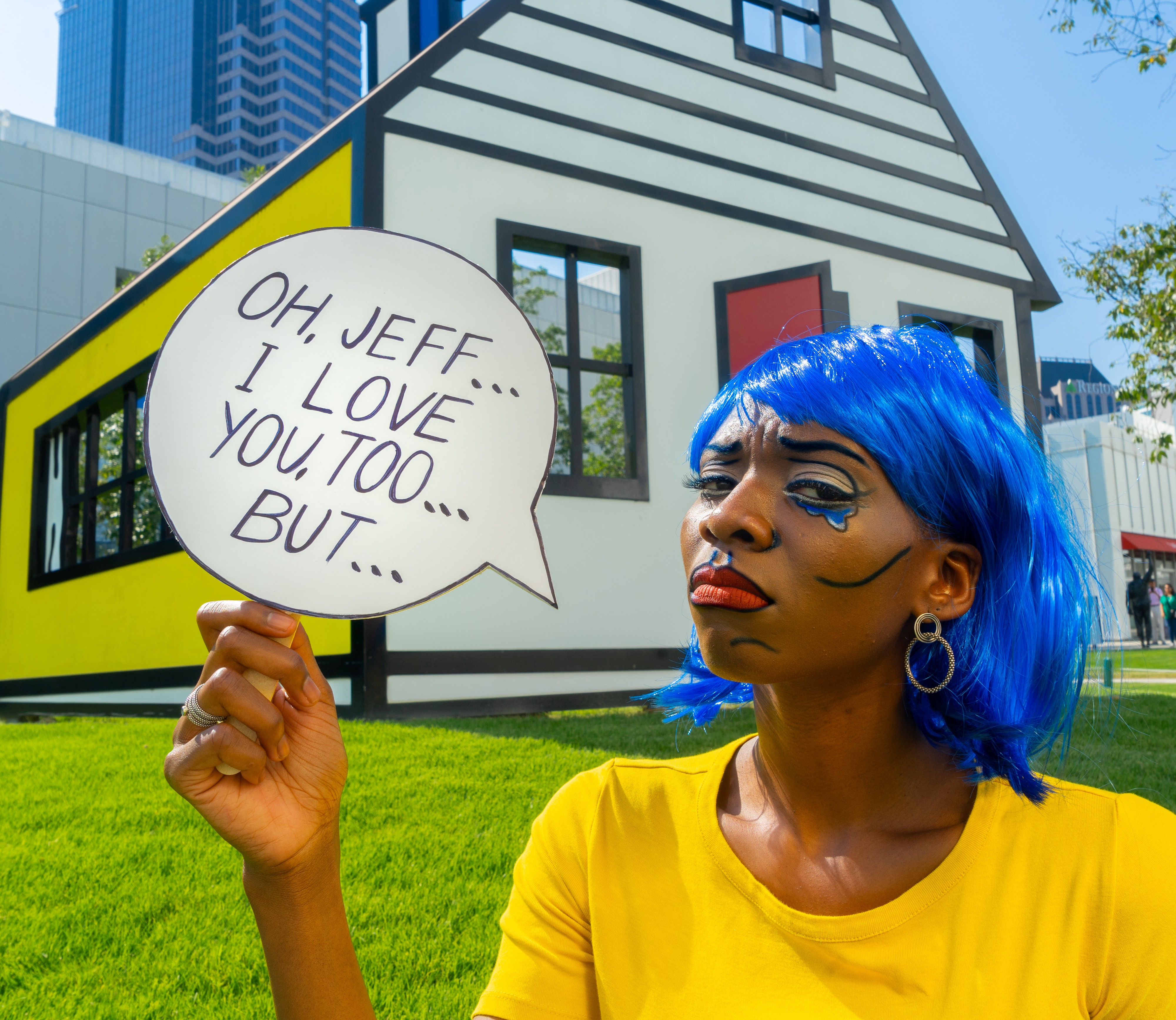 """A young black woman with comic style makeup and a blue wig holds a speech bubble saying """"Oh, Jeff, I love you, too but…""""."""