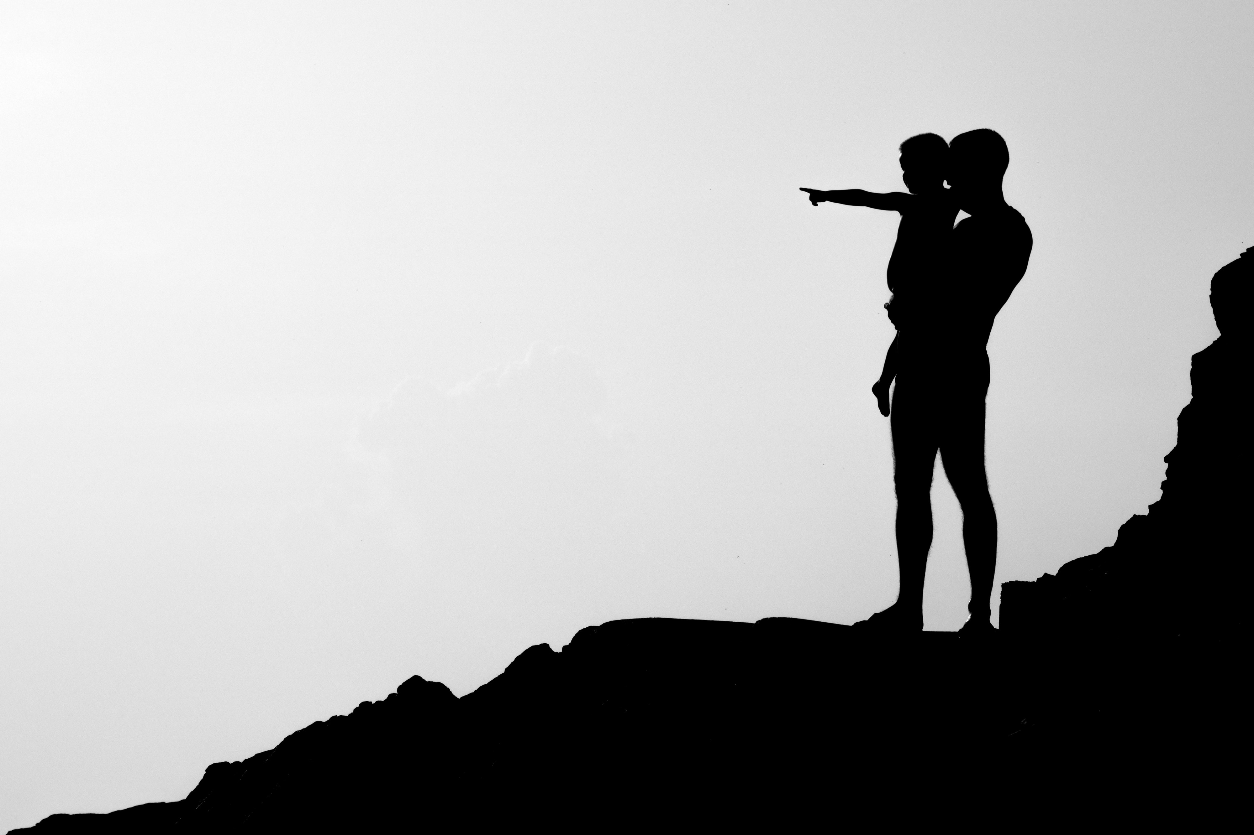 black and white photo silhouette of man holding child standing on rocky hillside child pointing