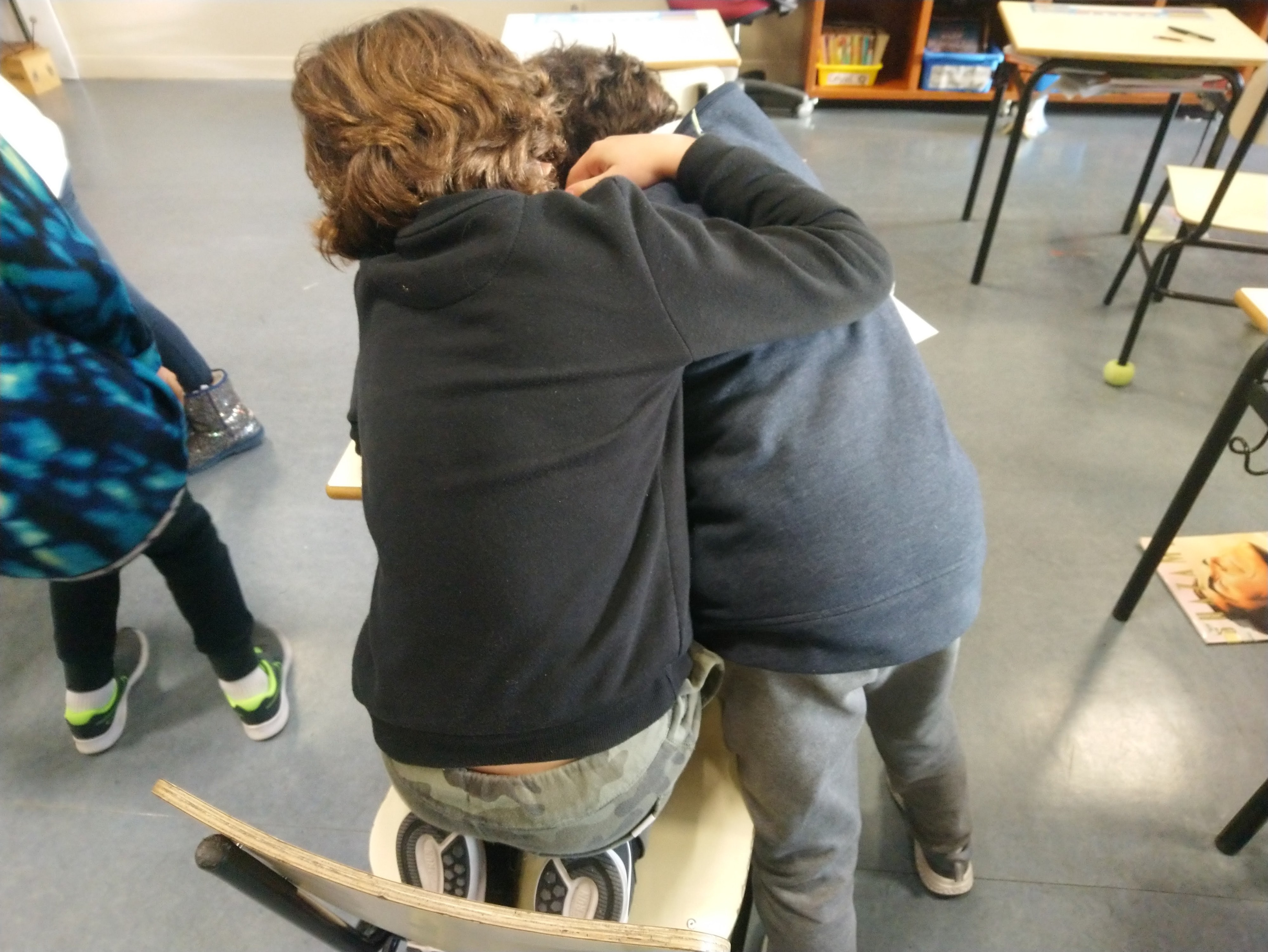 A student puts their arm around another in a classroom