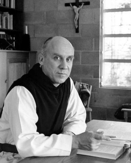 Thomas Merton in black and white Trappist monk's habit, seated at desk holding a pen over an open book.