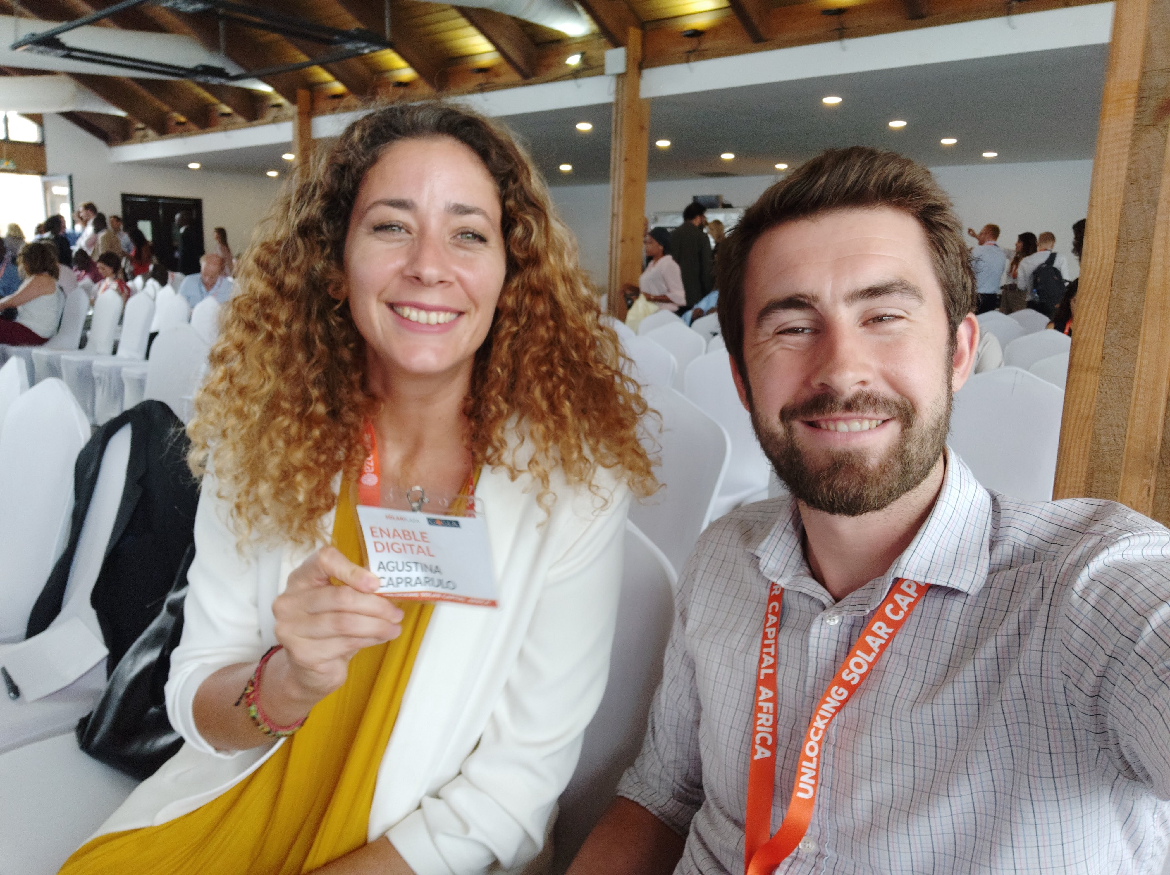 Agustina and Andrew, two Solution Consultants, sitting in the conference hall