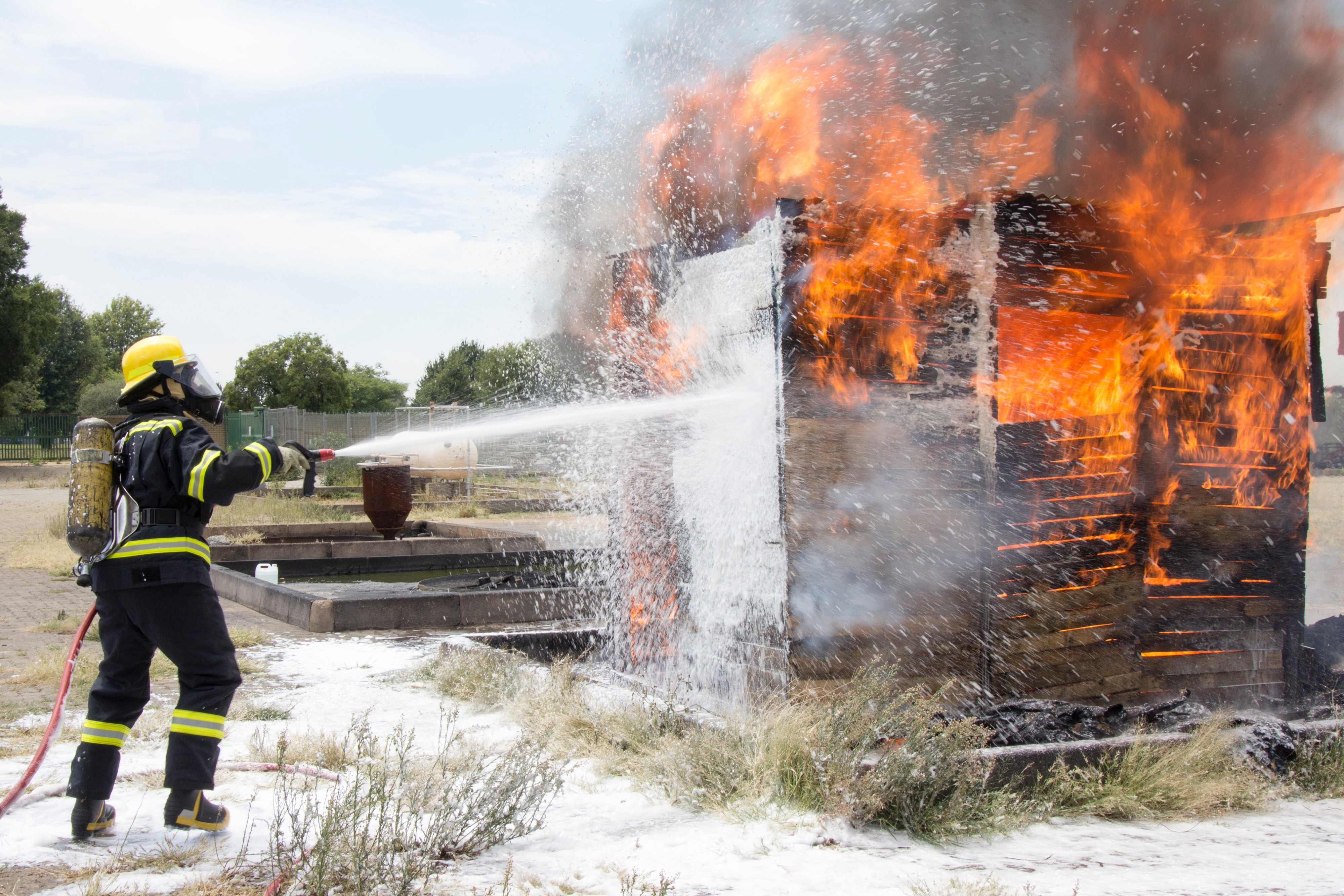 A fireman putting out a practice fire made of wood with a foam spray.