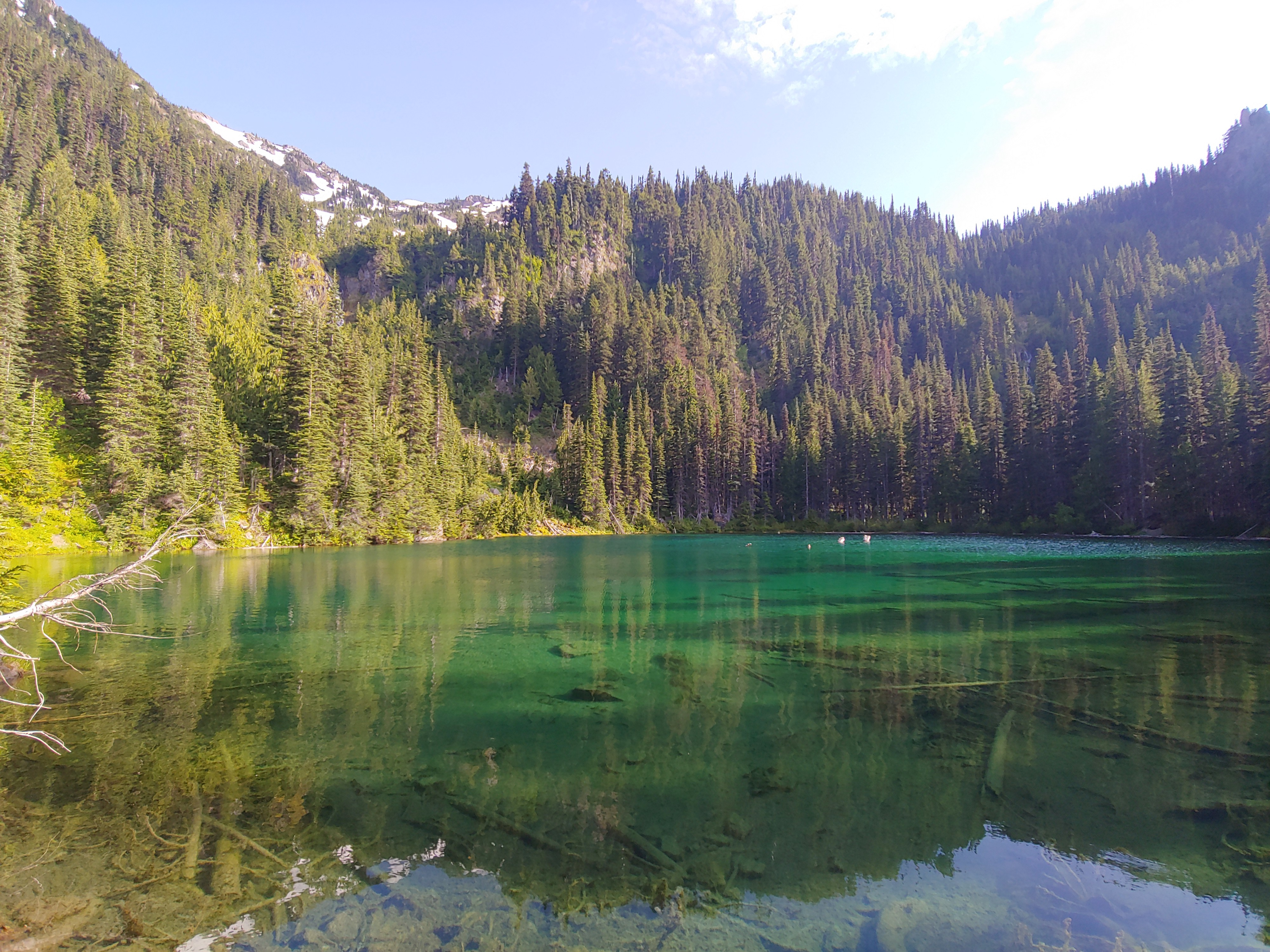 The crystal-clear waters of PJ Lake in Olympic National Park are nestled in a mountain bowl.