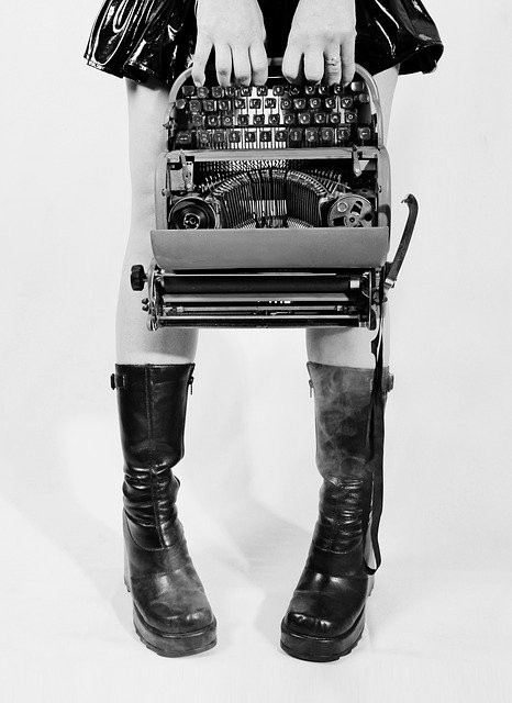 B/W image of girl in kinky boots carrying a typewriter