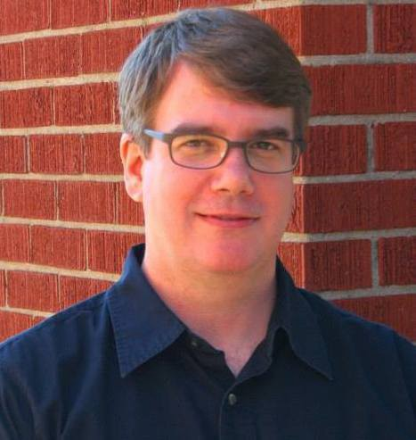 A closeup photo of a person with short brown hair, glasses, wearing a dark blue shirt.
