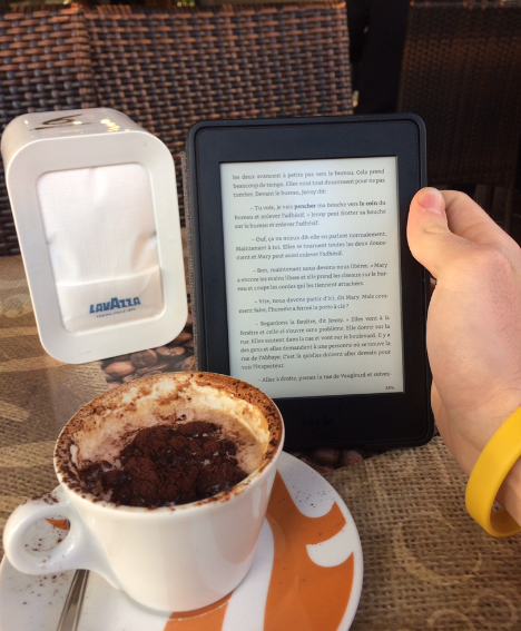 Author reading French on Kindle reader with coffee in Italy.