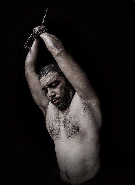 A shirtless Black man with his eyes closed and hands tied above his head in the dark.