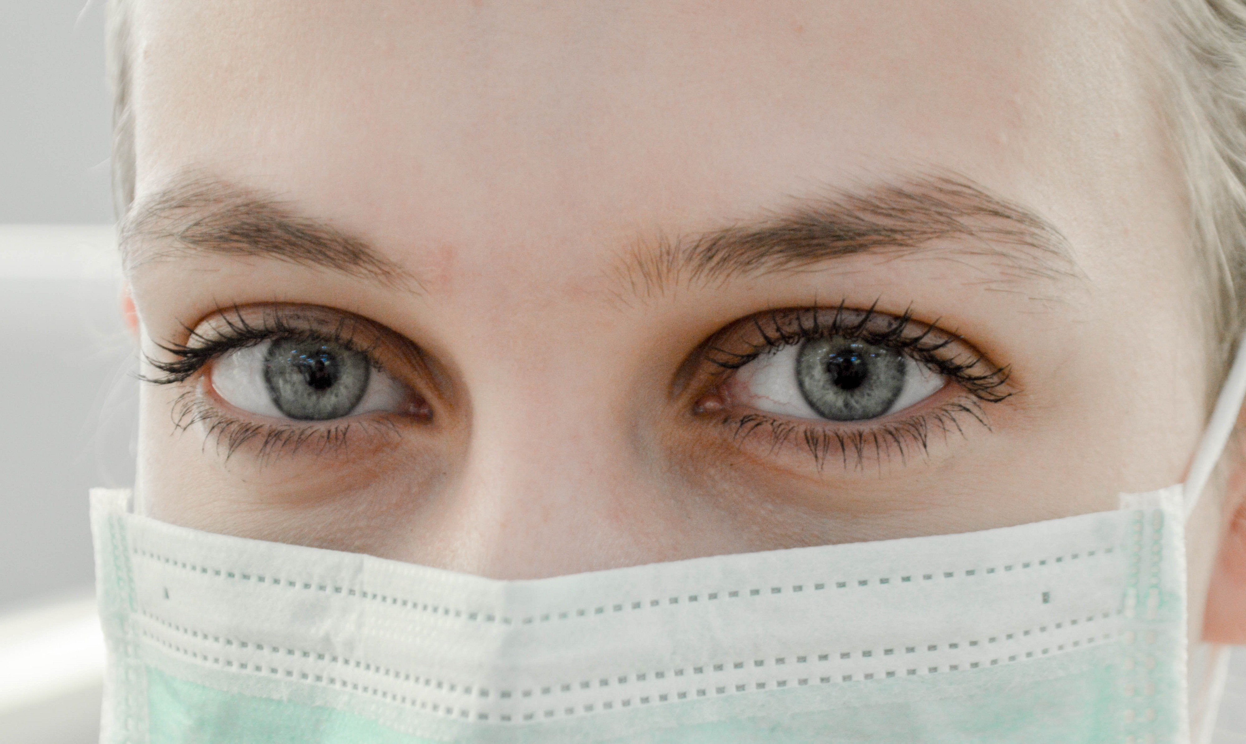 A zoomed in photo of a woman with blue eyes wearing a protective face mask