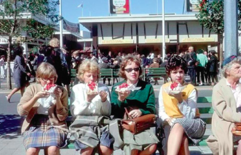 Fairgoers at the 1964–65 World's Fair, sitting and eating Belgian waffles with whipped cream and strawberries.