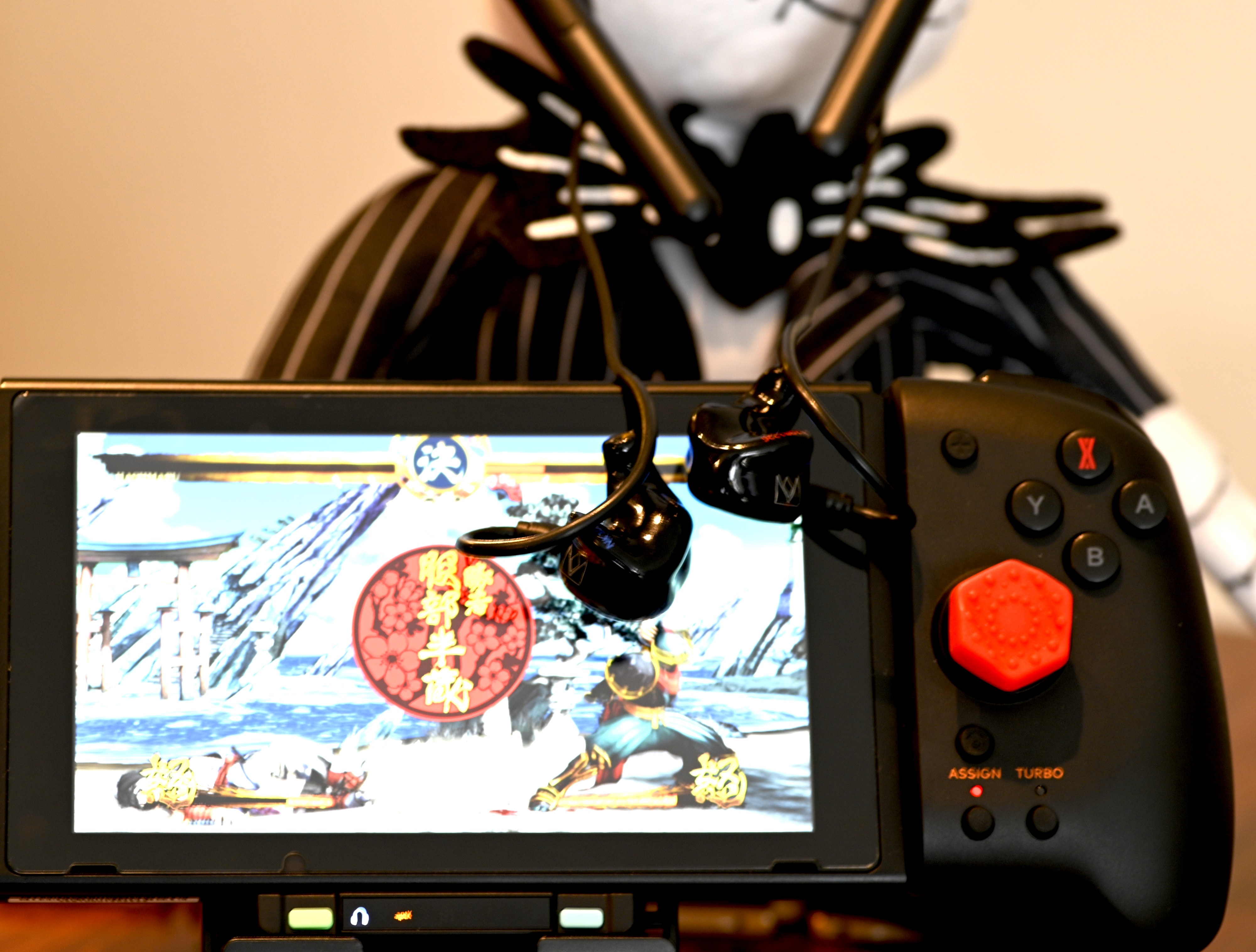 A Nintendo Switch in handheld mode showing off a pair of IEMs hooked up to the Fiio LC BT-2