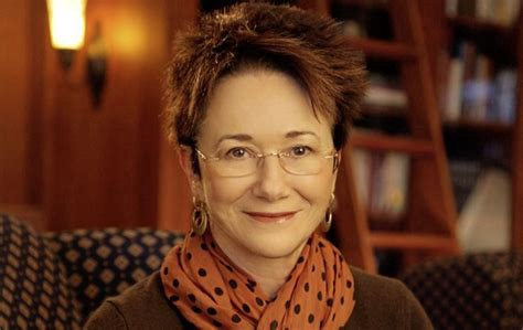 headshot of white woman with short spiky brown hair wearing orange scarf w black polkadots and rimless eyeglasses. big earrings. smiling at camera. she's sitting in a library with a ladder for reaching books.
