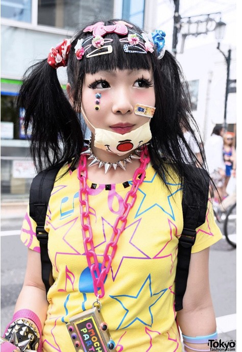 A woman wearing Harajuku style and a face mask with cartoon on her chin.