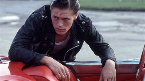 Willem Dafoe leans over the side of a cherry red convertible.