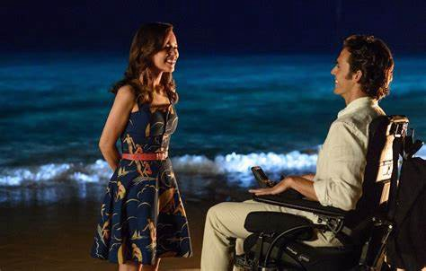 A scene from Me Before You. A white man in an electric wheelchair talks to a white woman standing in front of him.