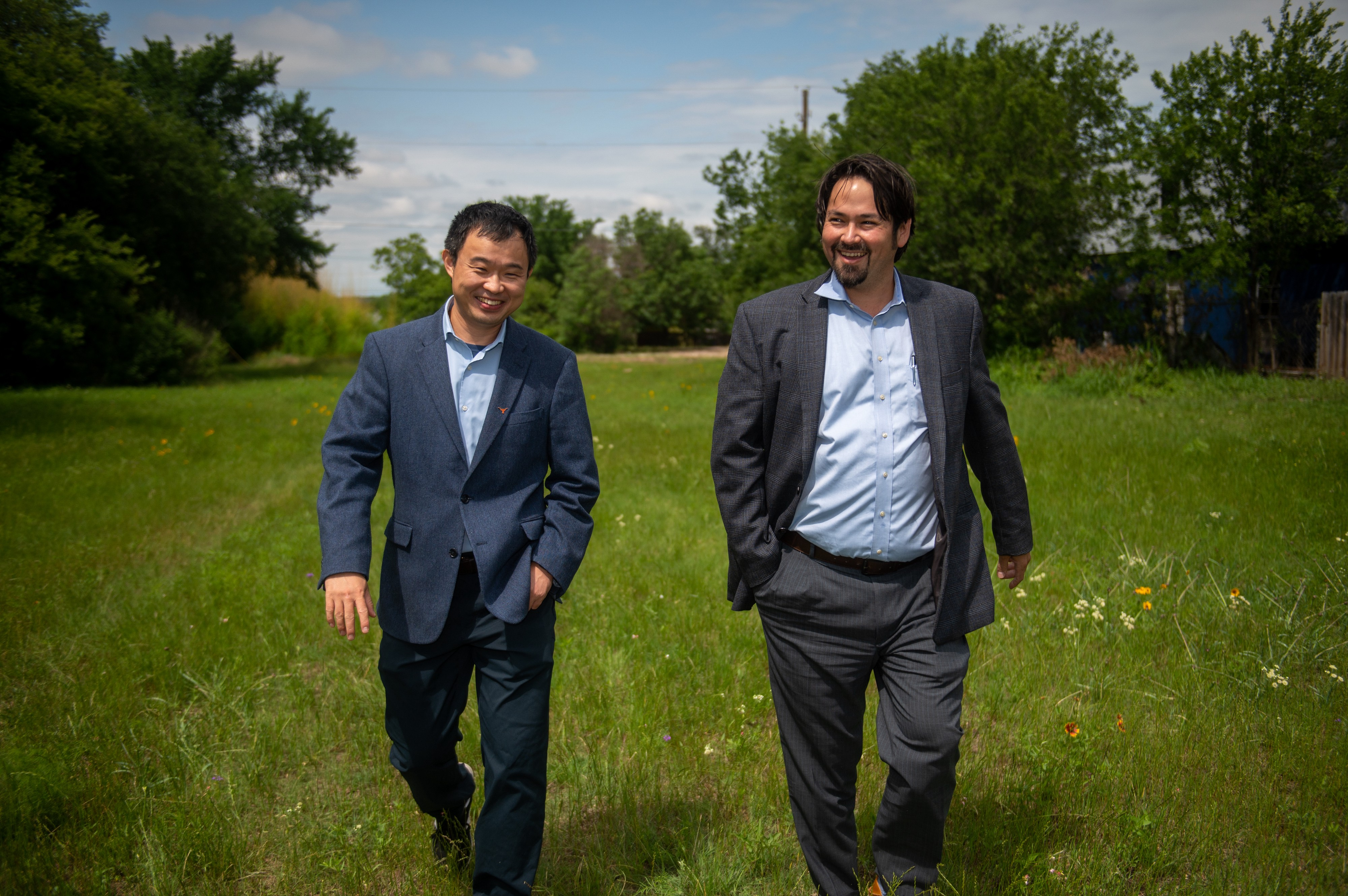 Two men, one a professor and another who works in transportation, walk through a grassy field where they plan to build a mobility hub.