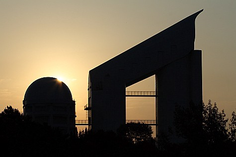 A telescope and dome, shilloetted by the Sun.