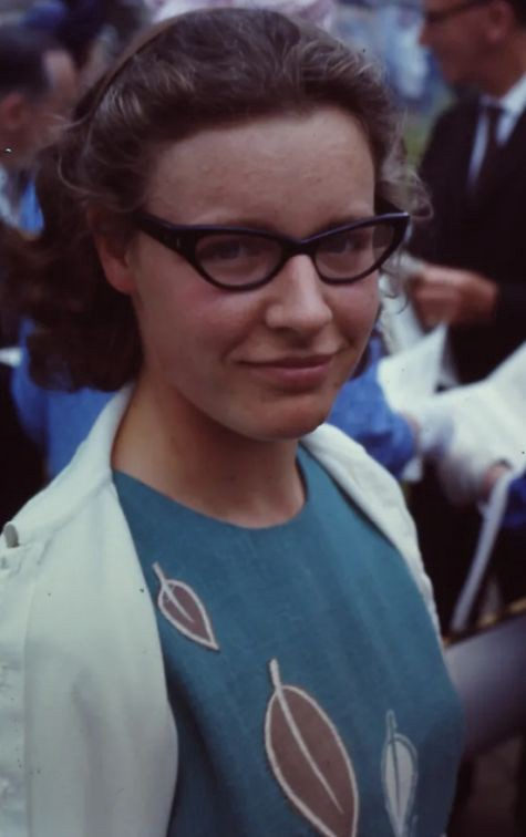 A woman with horn-rimmed glasses glances toward the camera.