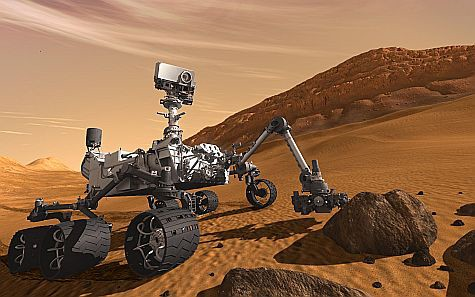 AN illustration of a car-sized robot on wheels and tracks traveling on Mars