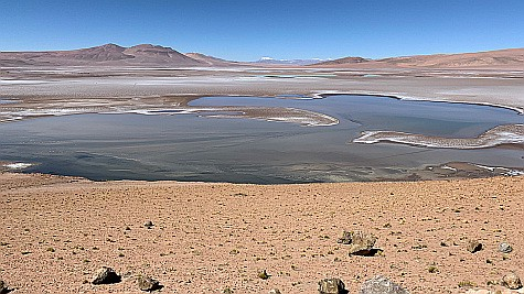 A dry, flat plain with a shallow body of water.