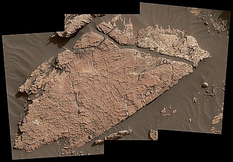 A flat, red rock, surrounded by darker crust.