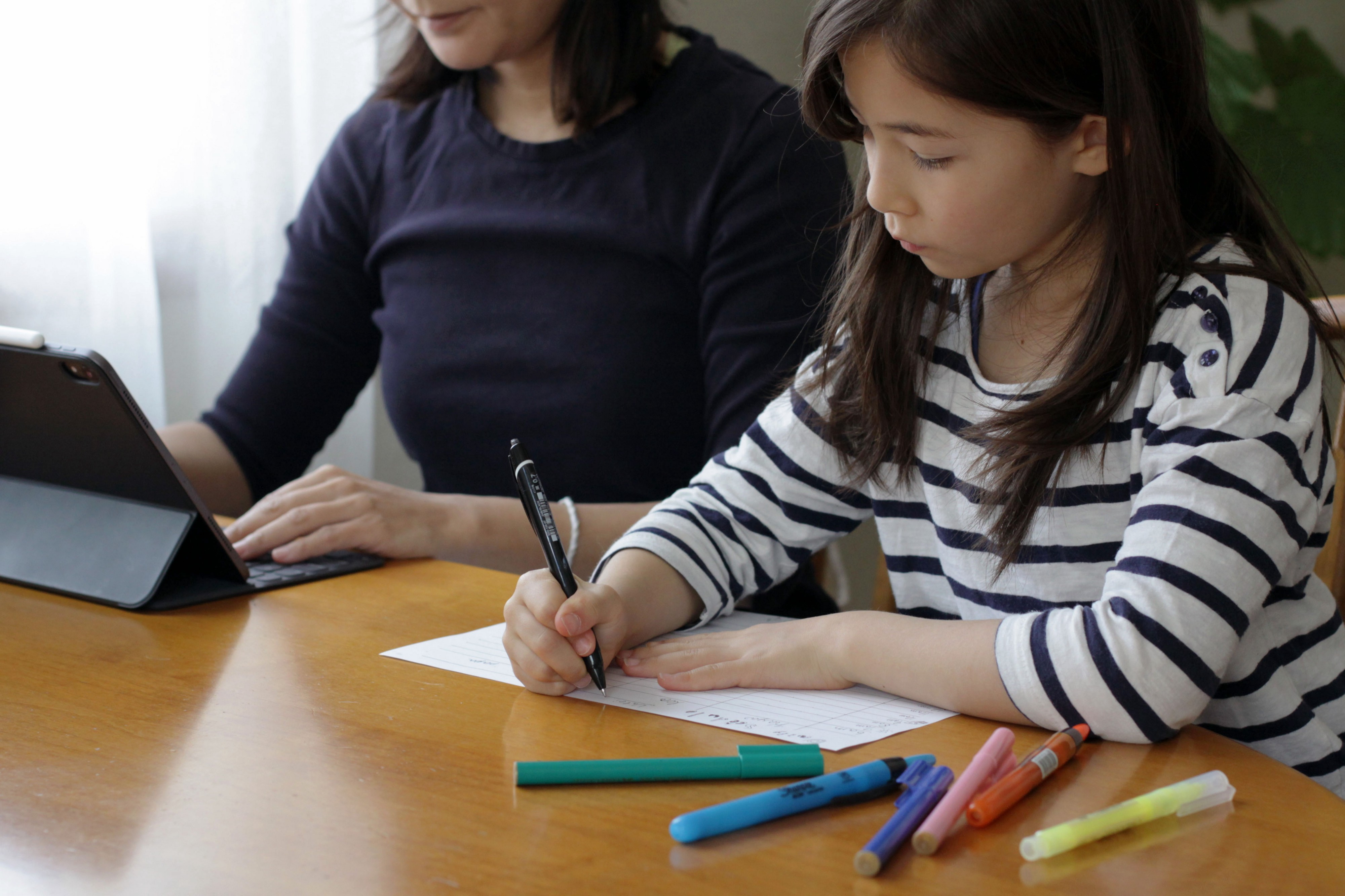 A young girl sitting with her mother at a table at home, creating her daily schedule.