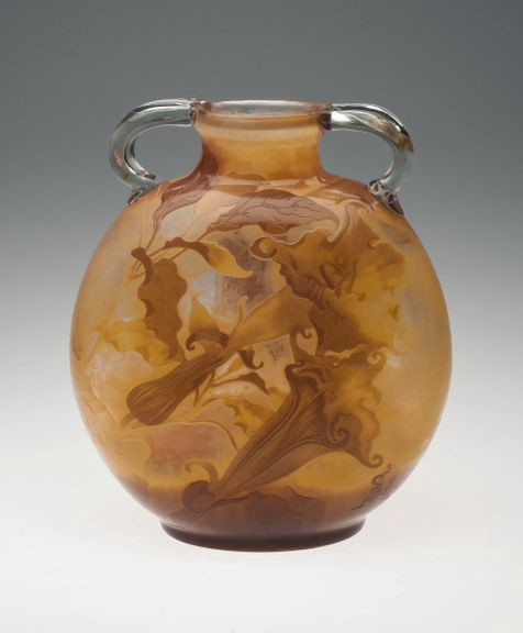 Honey colored vase with floral designs and two handles.