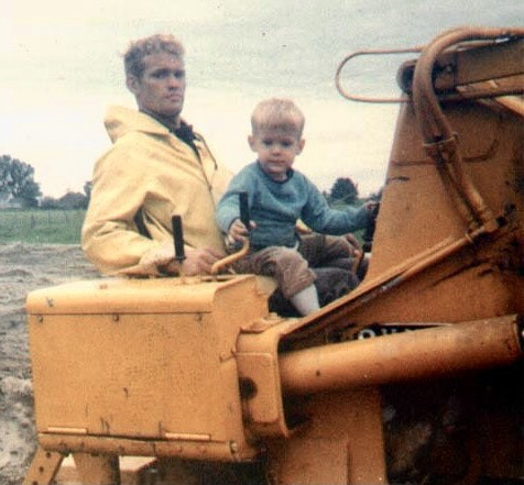 Author as young child with his dad on a yellow bulldozer in 1960s.