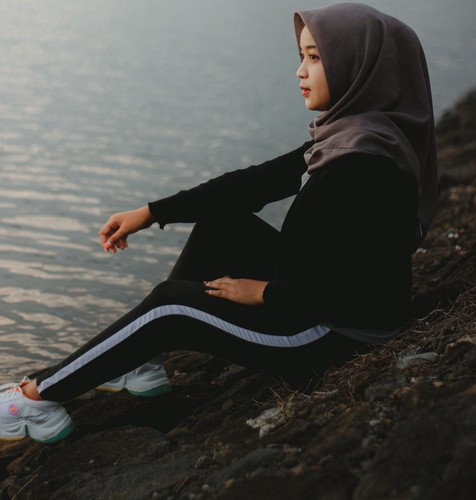 a young woman with a dark grey hijab, black athletic outfit with white shoes that have the red india circle on the shoes