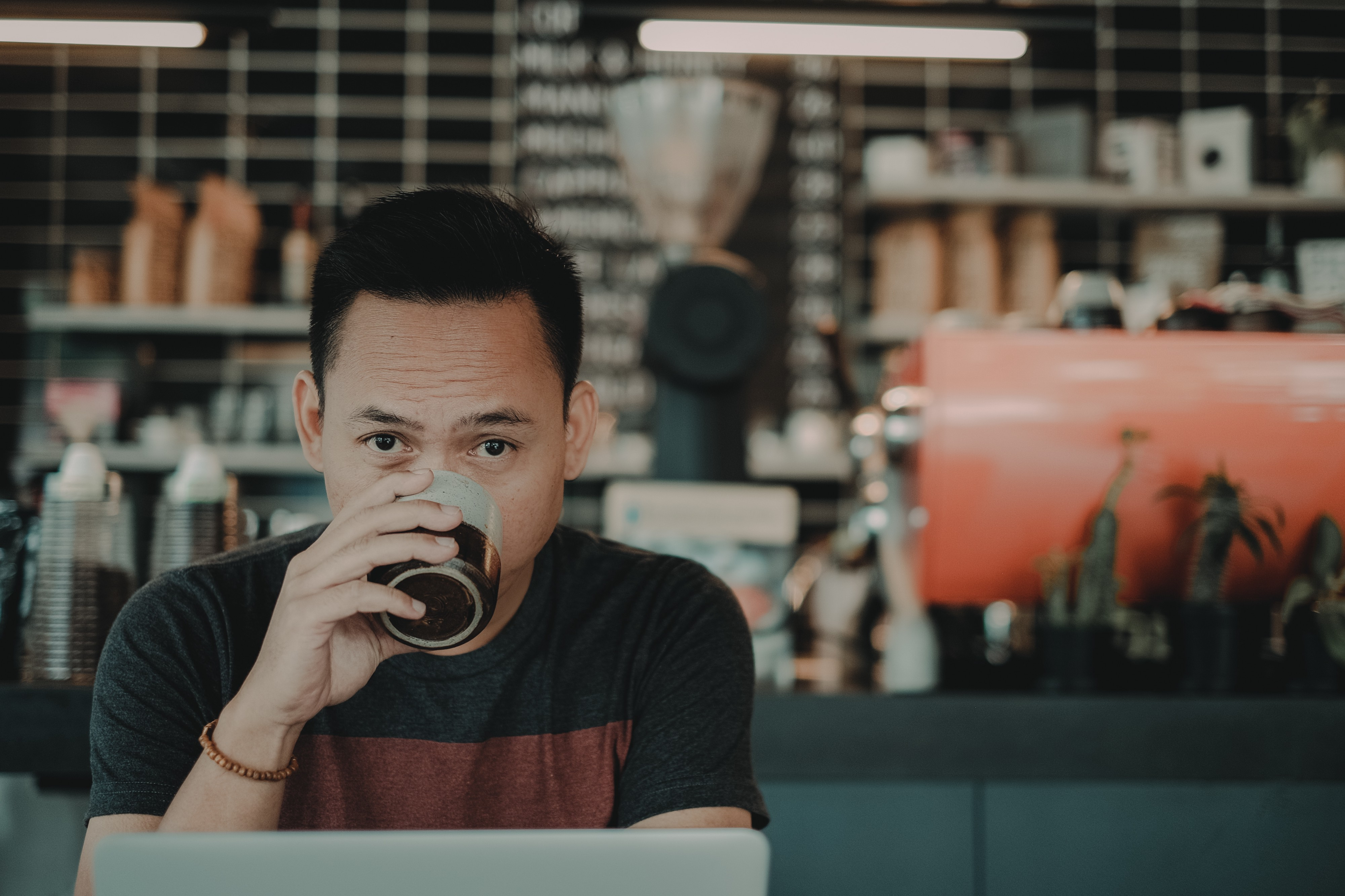 Man of Asian origin with short hair behind laptop drinking coffee in a retro-style cafe looking directly into the camera.