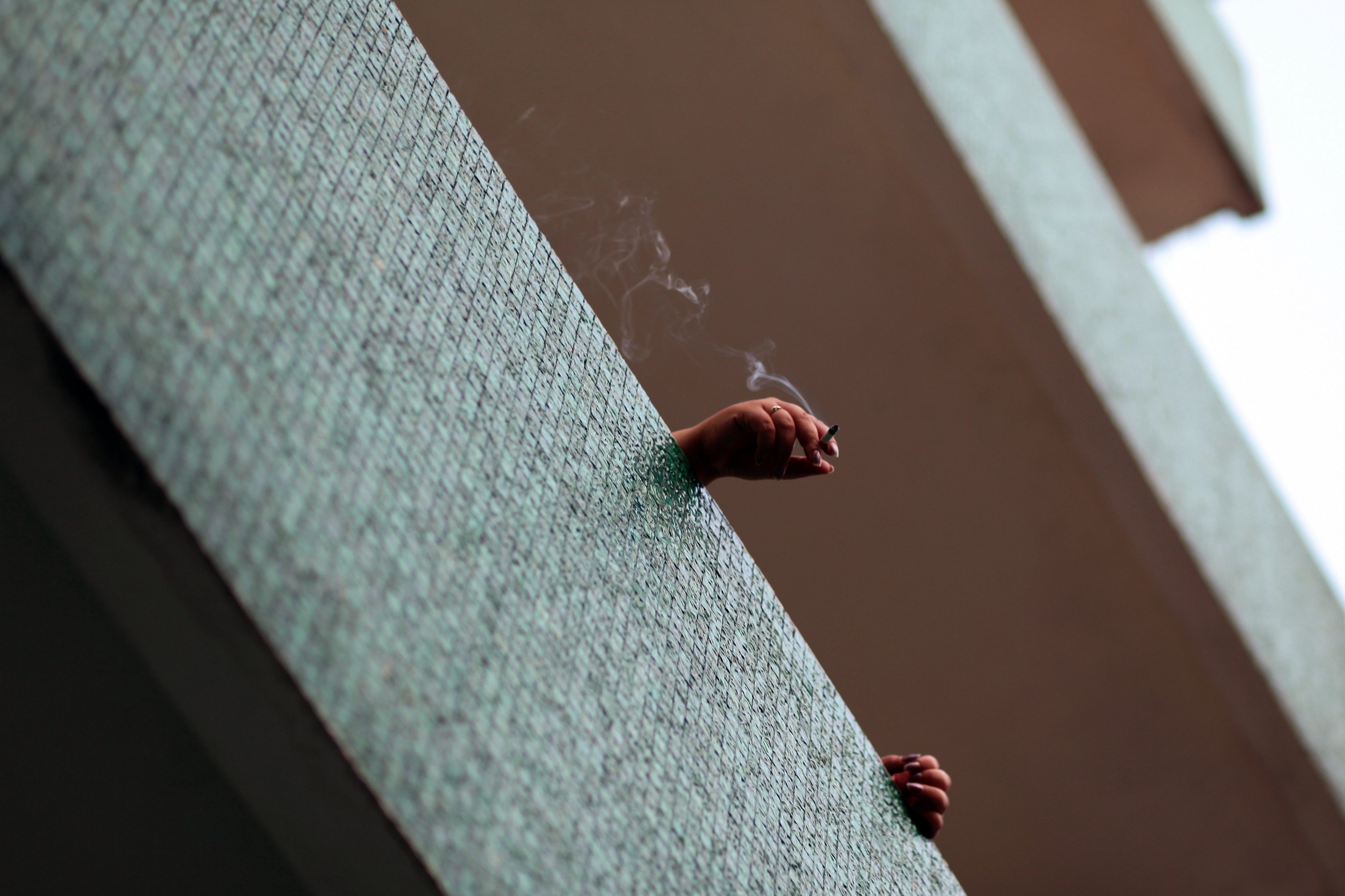Photo of hands, balcony and cigarette.