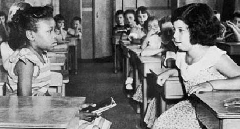 Black and white girls looking at each other in a classroom. Probably in the late 1950s.