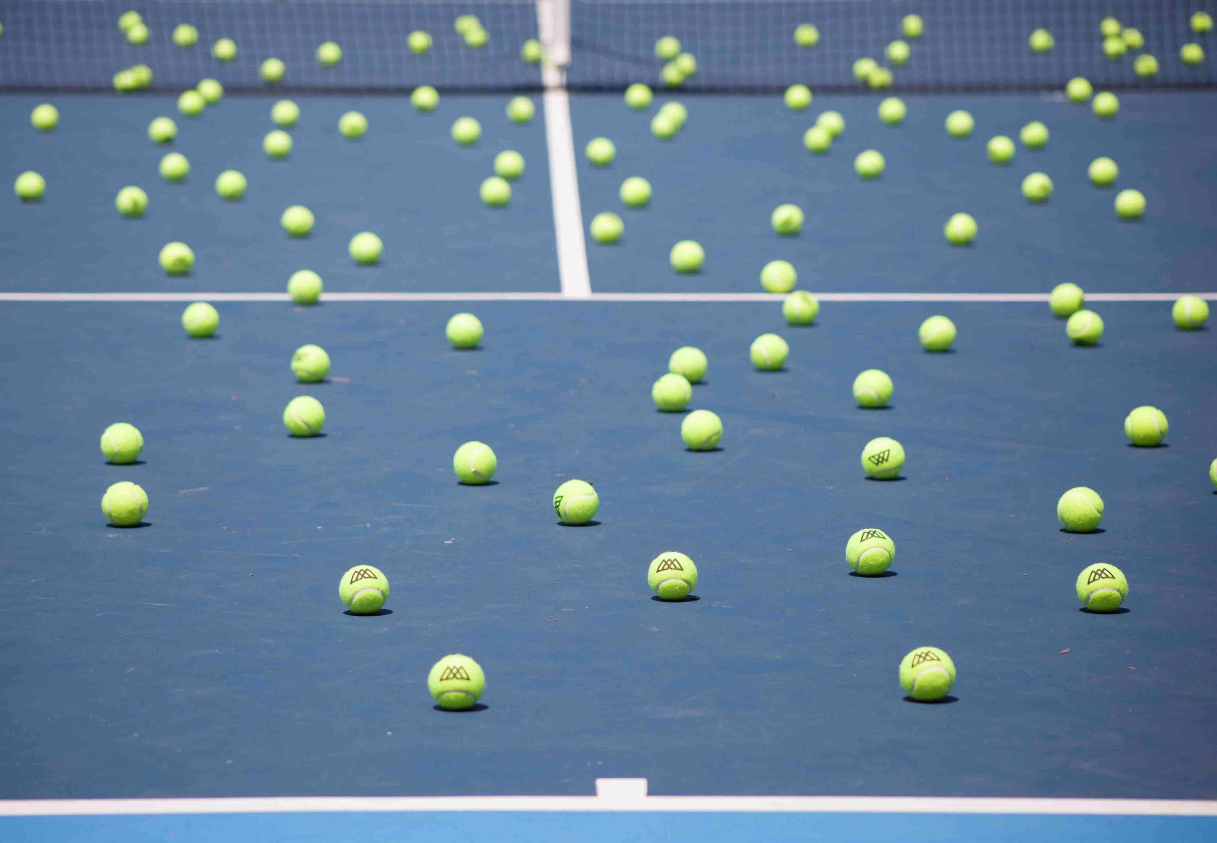 Many tennis balls on the ground